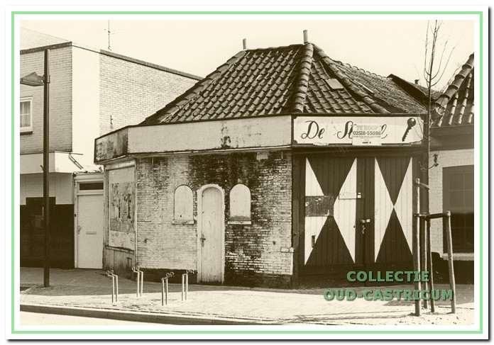 De voormalige doorrijstal omstreeks 1987 na de verhuizing van firma 'De Sleutel 'naar de Torenstraat. Het pand, dat er verwaarloosd uitziet, stond toen leeg. De naam 'De Sleutel' is overgeplakt mei de mededeling 'Te Koop '.