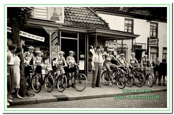 De herenmodezaak van Mul, Dorpsstraat 47, in 1957. Jan Mul voor zijn zaak te midden van de door hem gesponsorde wielergroep in de 'Tour de Flevo'.