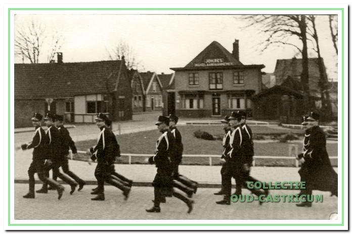 De marechaussee van de groep Castricum in ceremonieel tenue marcheert in de jaren 1943 door de Dorpsstraat.