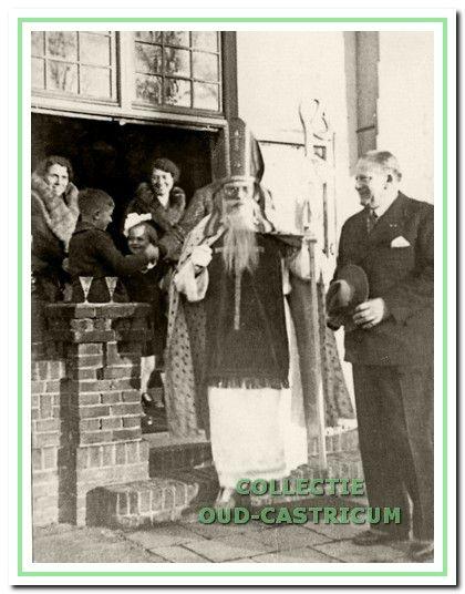Als Sinterklaas op bezoek bij burgemeester Lommen. In de deuropening mevr. Lommen en mevr. Leenaers met kinderen.