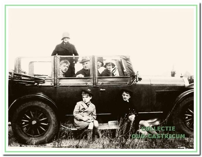 De familie Grond in de auto 'het kasteel' met open kap en houten spaken; links op de treeplank de verteller.