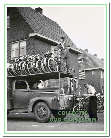 De Ford-vrachtwagen wordt geladen met fietsen, bestemd voor kampeerterrein Bakkum: Cor de Wit en op de luifel Jan Rozemeijer.