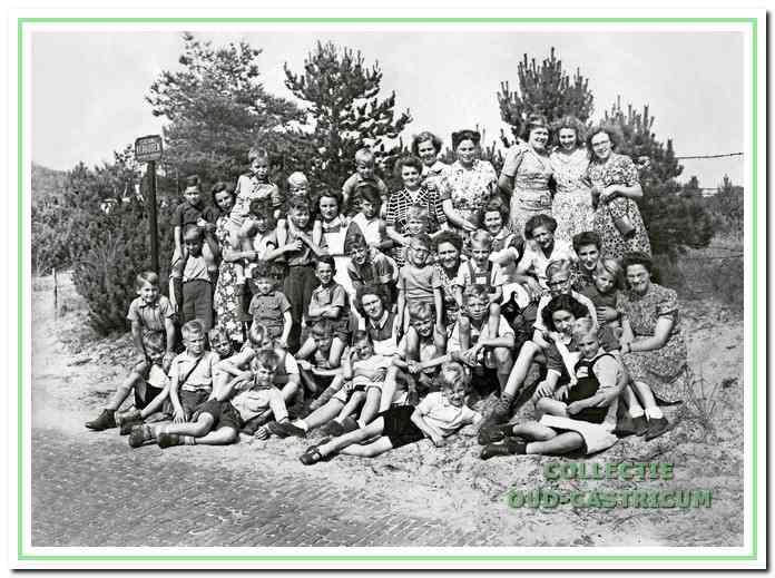 Een groep jongens met hun leidsters, enkele stafleden en dienstpersoneel poseren ergens in de duinen. De dame in de zwarte jurk met witte strepen is juffrouw Annie, onder haar directrice Bierman en uiterst rechts zit Ida Bollen.