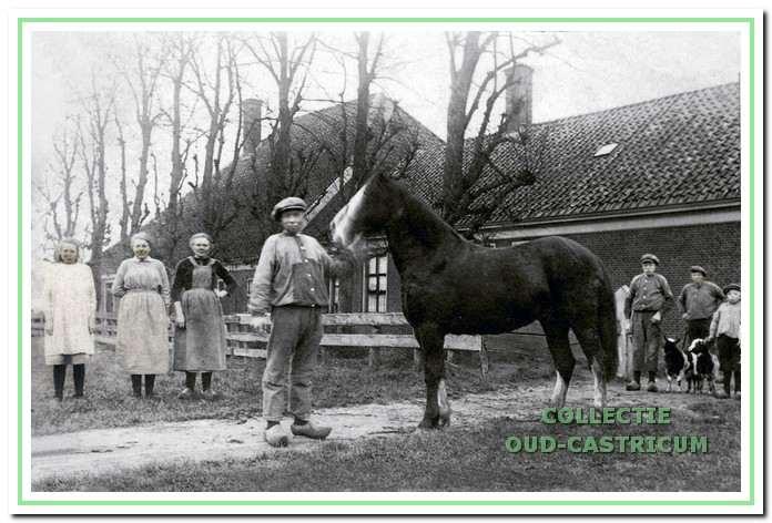 Cor Poel met paard voor de boerderij, achter hem zijn zussen en broers.