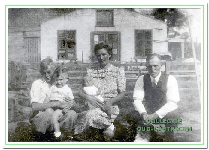 Anna Lute Borst en links zoon Jan met op schoot respectievelijk Kees en Siem Kuiper en rechts hun vader Siem Kuiper. Op de achtergrond de timmerwerkplaats van Tromp.