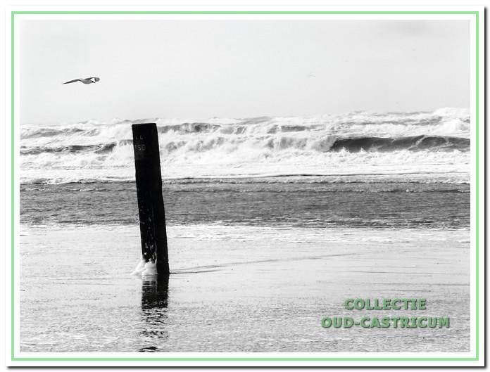 De woeste zee met strandpaal als monument voor de Wilhelmina Frederika en de heldhaftige redders.