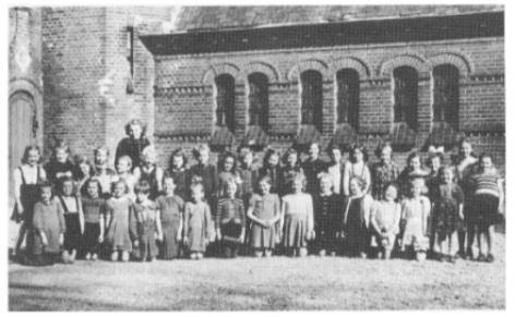 1947 Klas van de RK meisjesschool Maria Goretti voor de Pancratiuskerk met 'Juf' Juffermans.