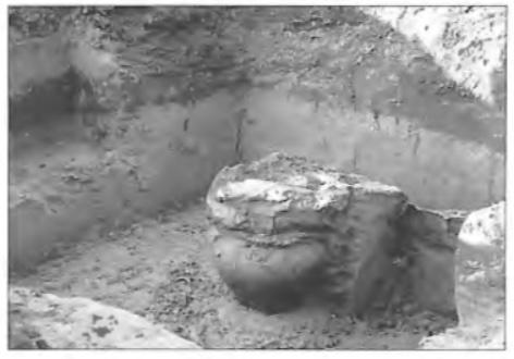 Twee met de randen op elkaar geplaatste potten. Duidelijk tekent de bewoningslaag zich af in het lichte zand.