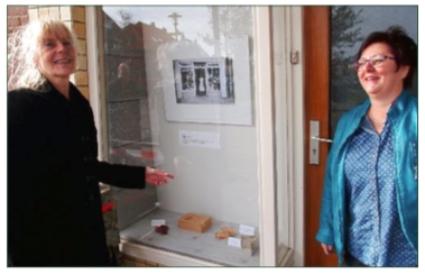 Werkgroeplid Erica Brouwer (links) met Karin de Winter voor de etalage met foto's van Oud-Castricum aan de Torenstraat 42.