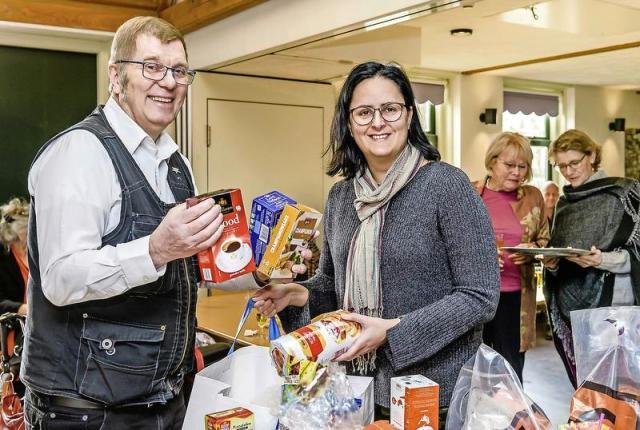 Geert Spiering krijgt van Jacha Hondius-Mesman levensmiddelen voor de Zaanse Voedselbank.