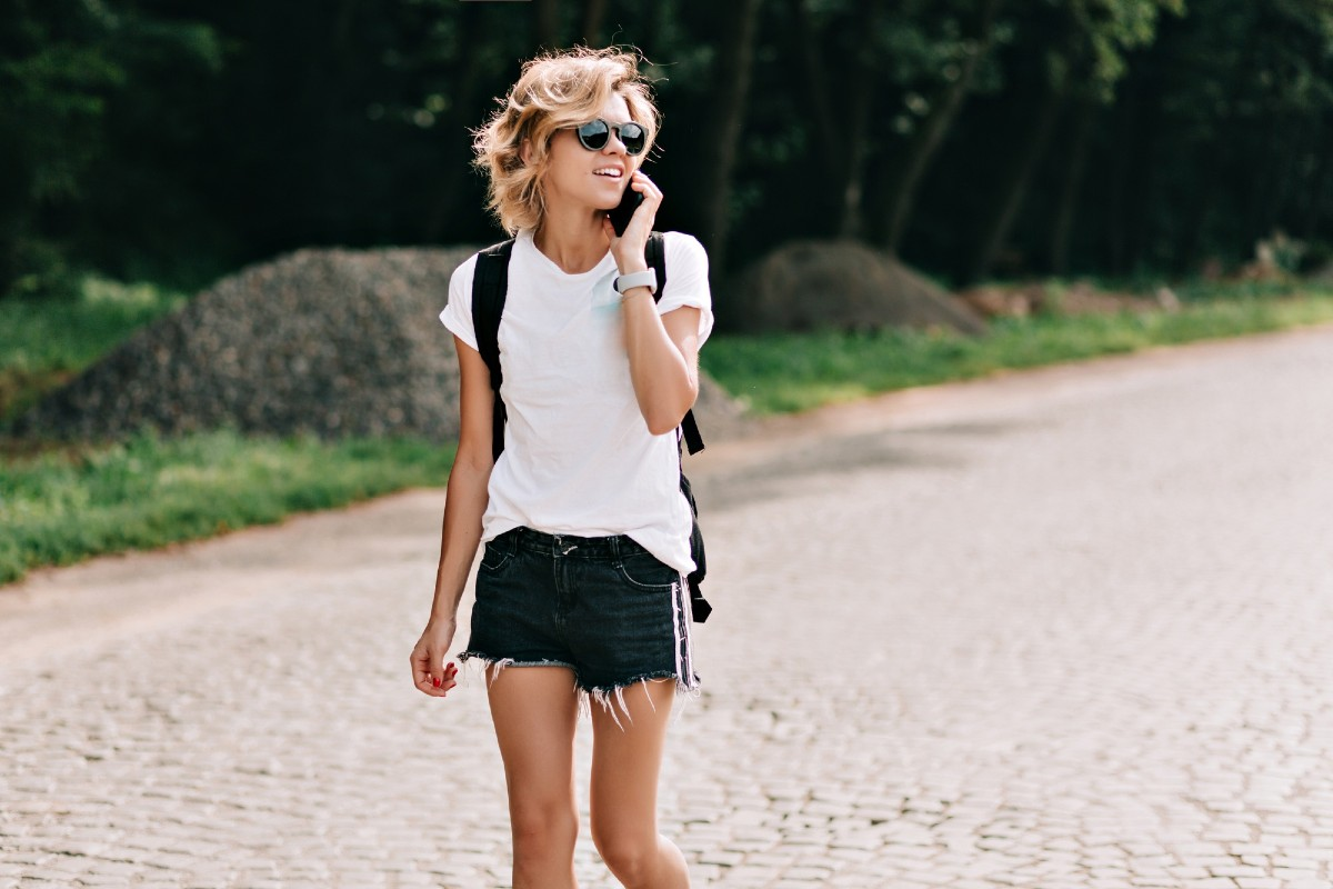 Young woman walking and talking over the phone outside
