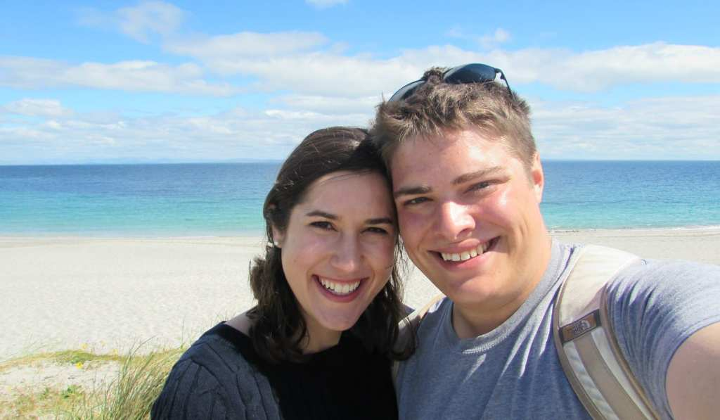 Selfie of Kate Storm and Jeremy Storm in front of a turquoise beach on Inisheer Island Ireland