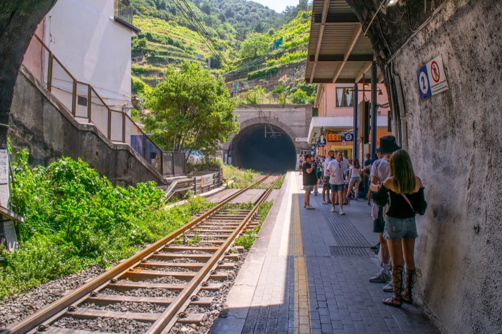Photo of the empty train tracks at a station in Cinque Terre. Some people are standing to the side and waiting on the platform.