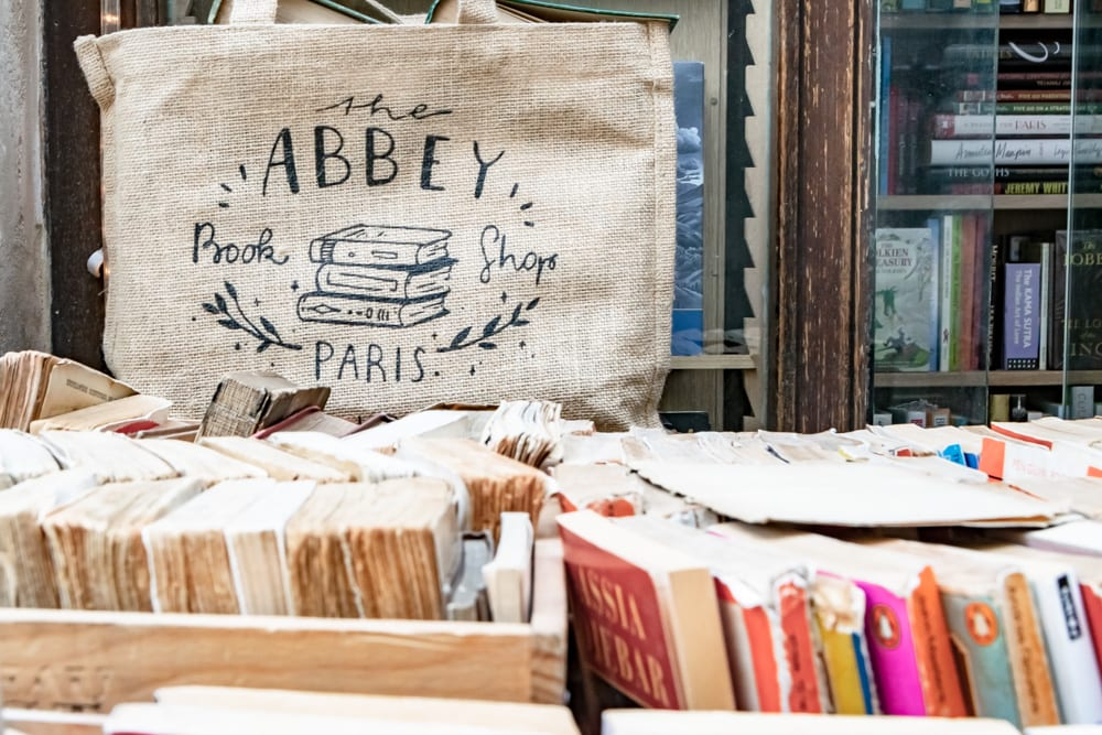 """Photo from Abbey Bookshop in Paris. There are the tops of spines of books visible in the foreground and a tote bag that says """"Abbey Bookshop"""" in the background."""