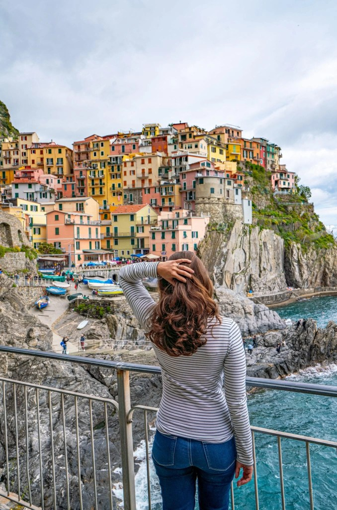 Woman facing away from camera on Manarola Promenade, One Day in Cinque Terre Itinerary