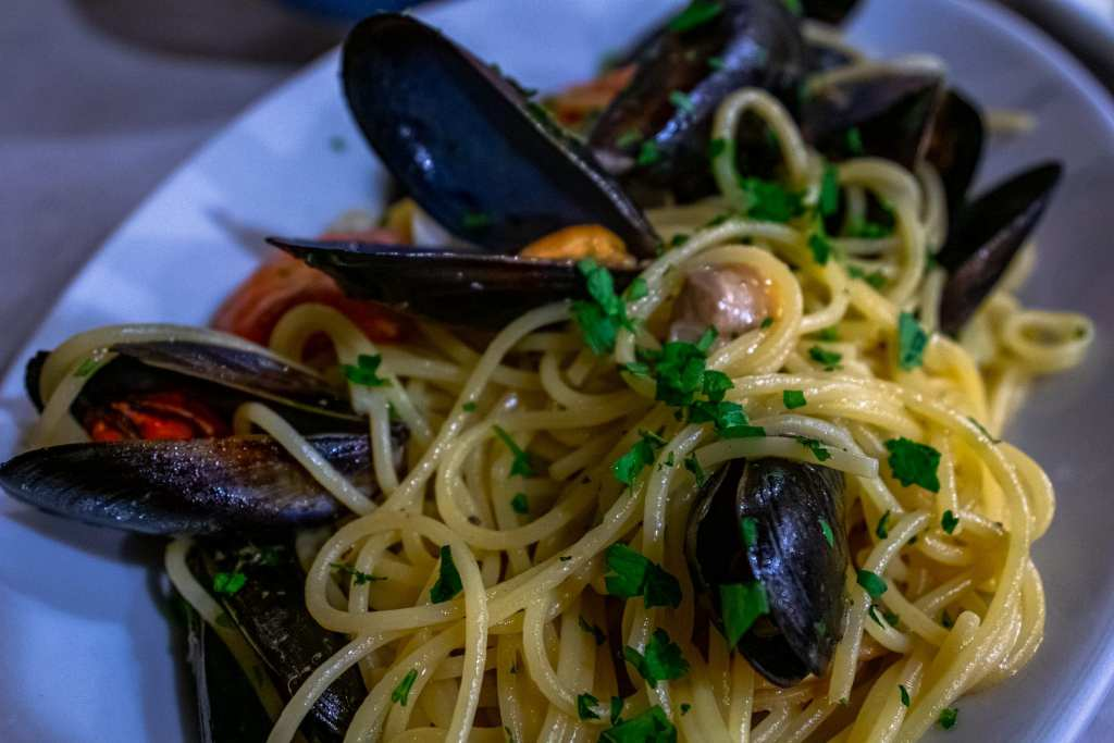 Plate of seafood pasta with mussels in it as served in Cinque Terre. Trying the seafood is among our many Cinque Terre tips!
