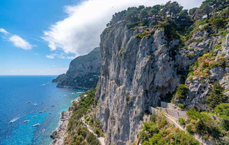 Cliffs of Capri with bright blue water and boats visible to the left. Definitely consider a visit here when planning a trip to Italy!