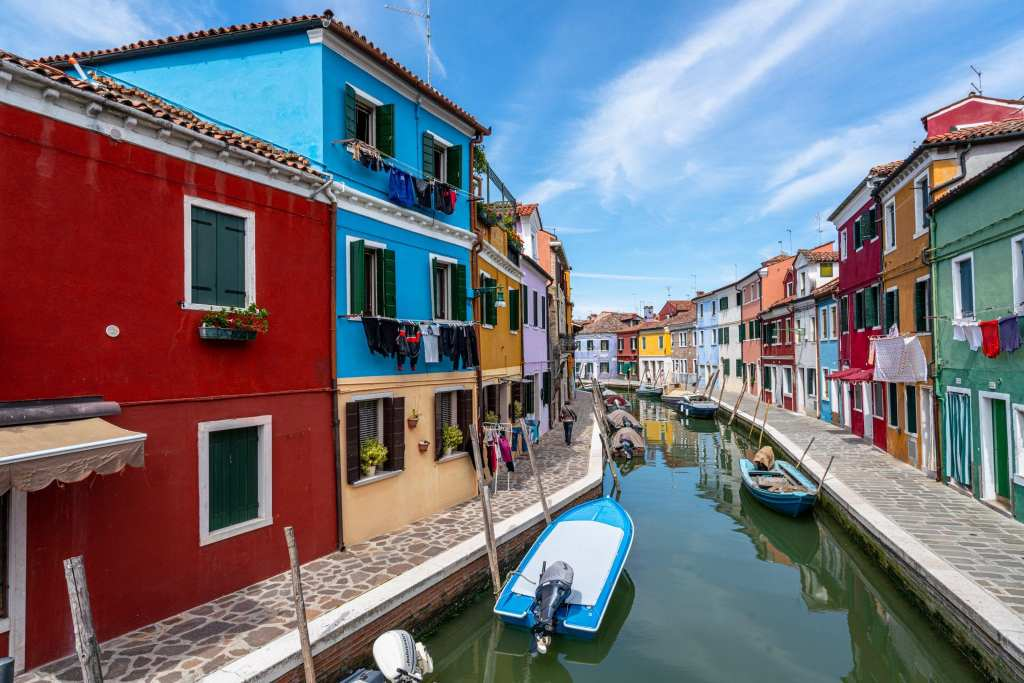 Photo of a canal of Burano with colorful buildings on both sides.