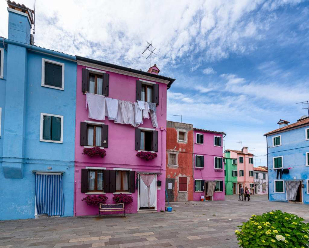 Photo of colorful houses in Burano as seen from a piazza. Laundry is hanging from some windows.