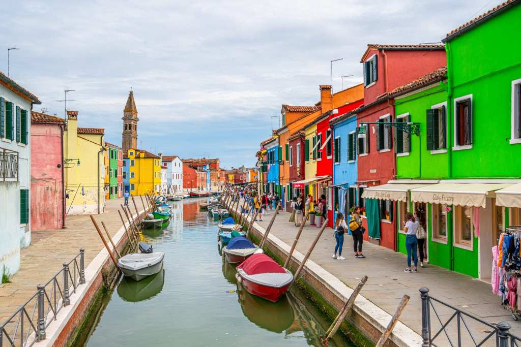 Photo of a canal in Burano with colorful houses on both sides and leaning tower in the background.