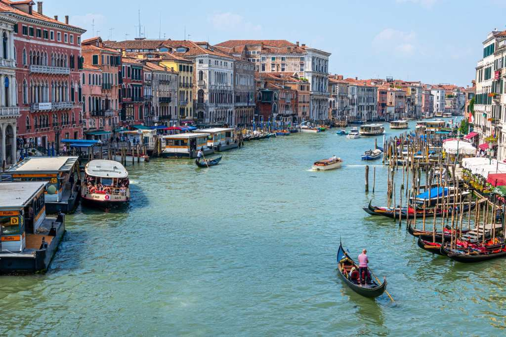 Photo of Grand Canal of Venice taken from Rialto Bridge, with a gondola in the bottom right corner--definitely find this view when spending one day in Venice!