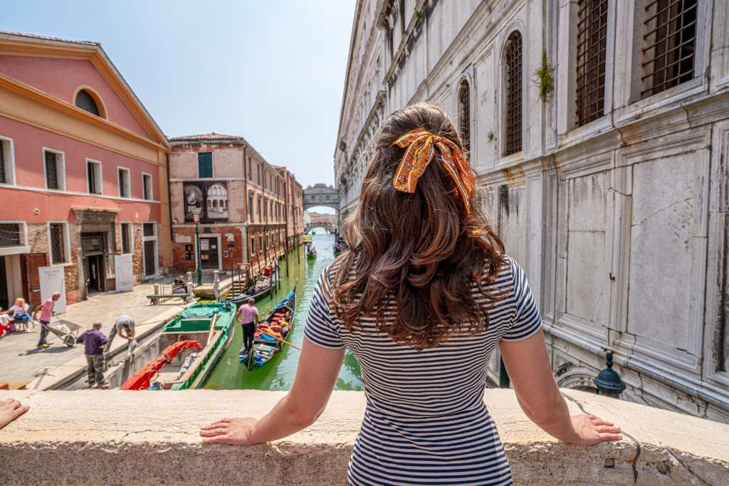 Kate in a striped dress in Venice looking toward the bridge of sighs--definitely worth seeing during one day in Venice! Kate has a yellow ribbon in her hair.