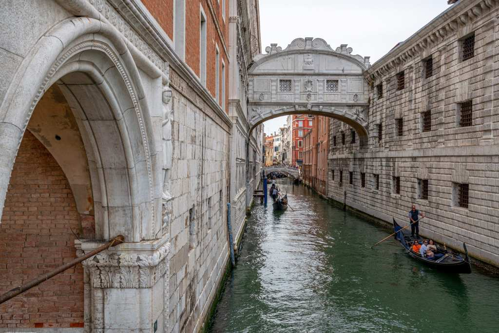 Photo of the Bridge of Sighs, with a few gondolas visible in the canal below.