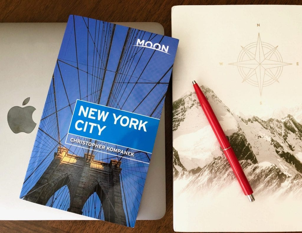 Photo of a Macbook Pro, a notebook with mountains on the cover, and a red pen. A copy of Moon New York City is laying on top of them--use this to find some of the best things to do in MIdtown NYC!