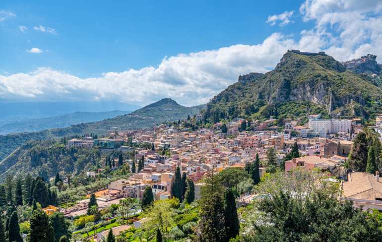 View of Taormina as seen from grounds of the Greek theatre. You can see the bottom of Mount Etna, the peak is covered by clouds.