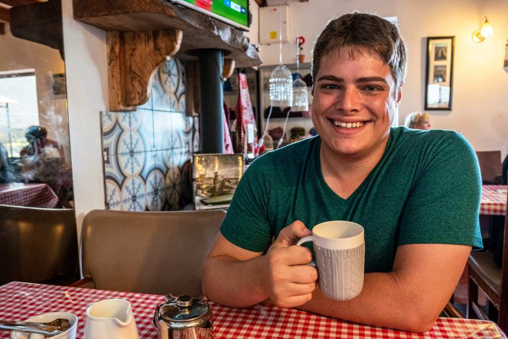 Jeremy Storm holding a cup of tea in a small cafe on Inisheer Ireland. There's a stone fireplace behind him.