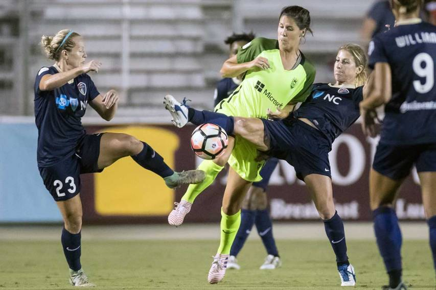 Kristen Hamilton (23), Katie Johnson (middle), and McCall Zerboni (right) vie for the ball. Muscles McCall. (Shane Lardinois)