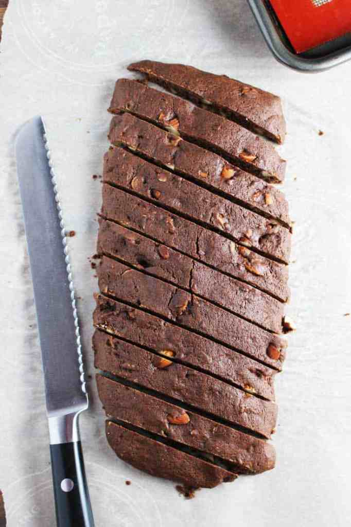 A sliced log of almond chocolate biscotti on parchment