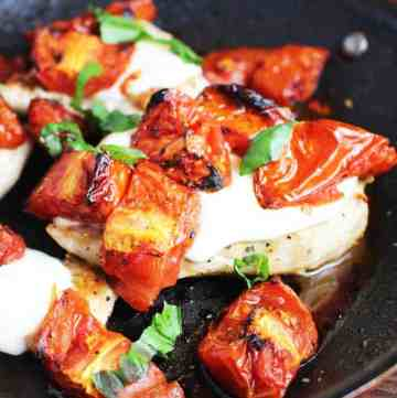 Cheesy caprese chicken in a pan with melted mozzarella, roasted tomatoes and basil