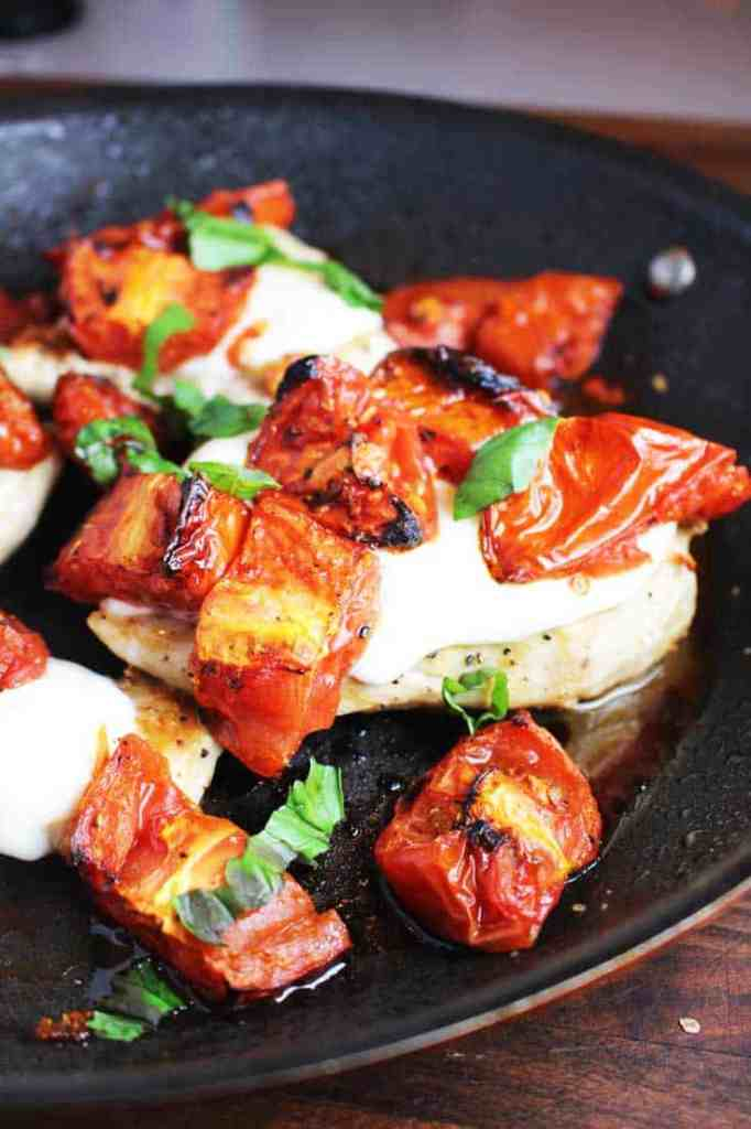 Cheesy caprese chicken recipe in a pan with melted mozzarella, roasted tomatoes and basil