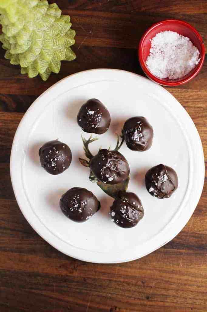 Overhead shot of seven Dark chocolate truffles with caramel, sprinkled with Fleur de sel, on a plate, with a Christmas tree candle in background