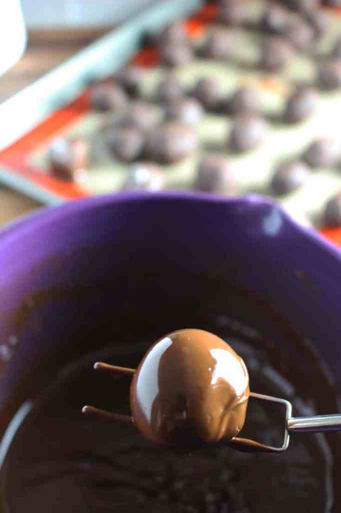 Dark chocolate truffle with caramel that was just dipped in chocolate, on a dipping fork above the bowl of melted tempered chocolate