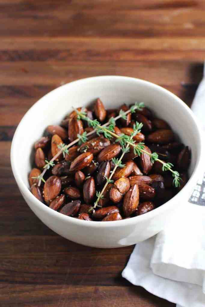 Roasted almonds in a bowl with thyme sprigs