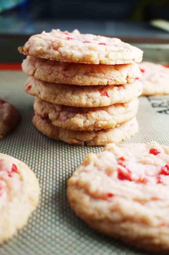 A stack of cherry almond sugar cookies on a baking mat