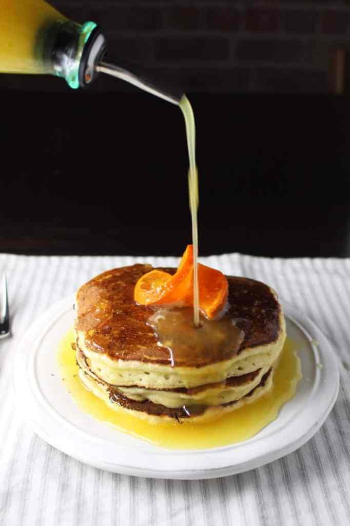 Stack of ricotta pancakes on a plate with orange syrup being poured on top
