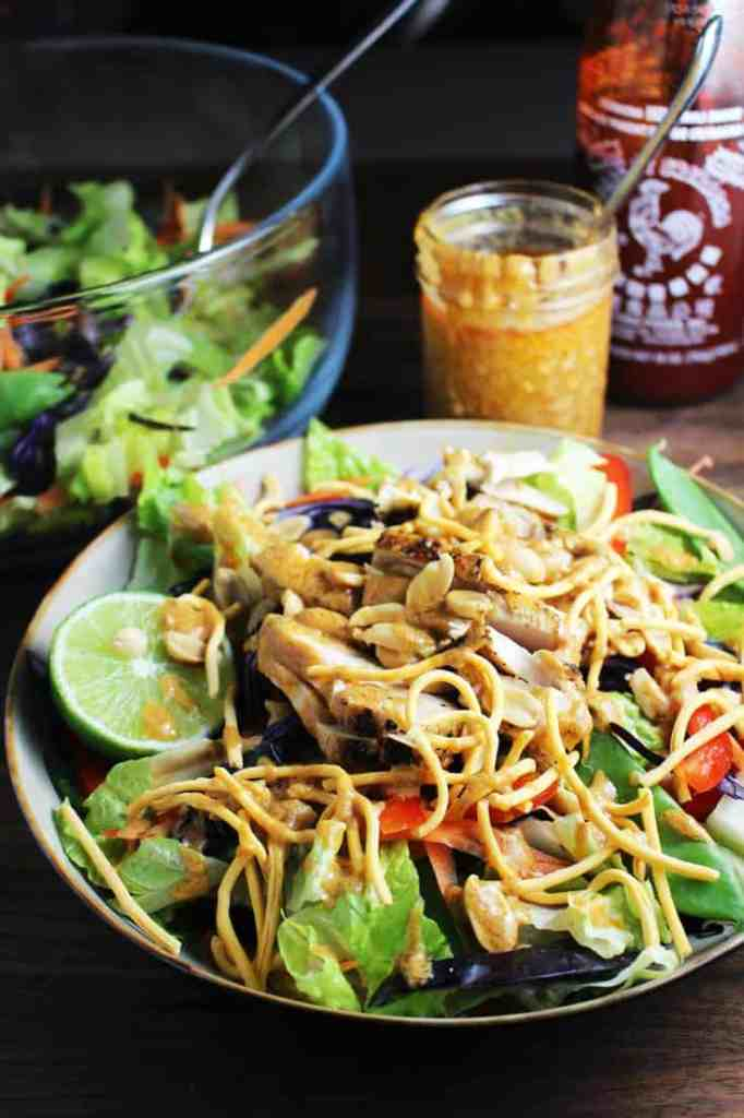 Asian chicken salad with sriracha peanut dressing in a bowl