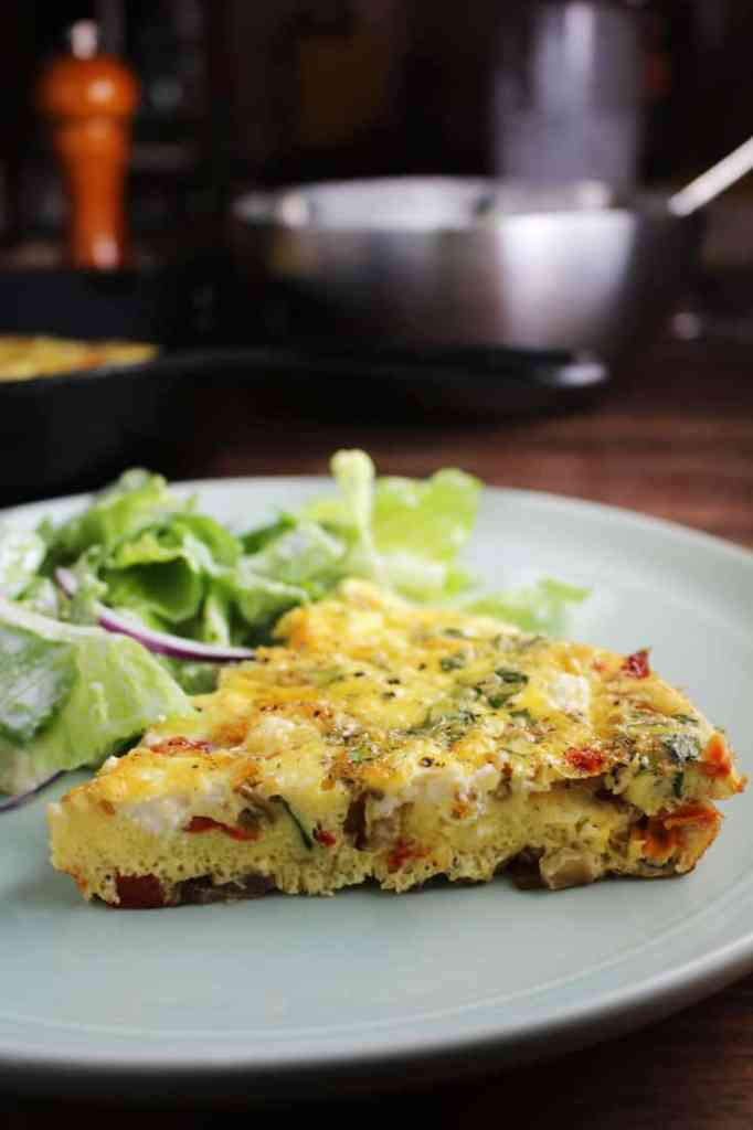 Side view of a slice of easy fritatta recipe on a plate with salad.