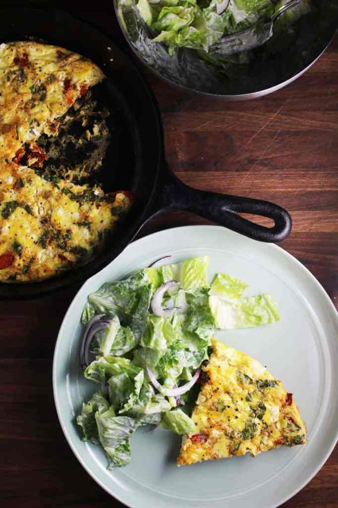 Overhead view of slice of easy fritatta recipe on a plate with salad