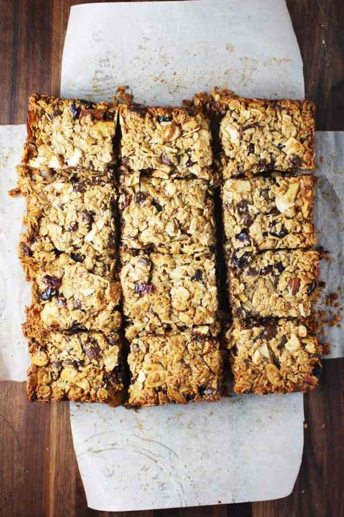 Freshly baked chewy granola bars cut into squares on a sheet of parchment