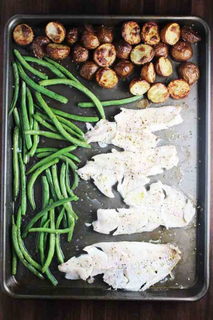 White fish, green beans and potatoes on a sheet pan for sheet pan dinner