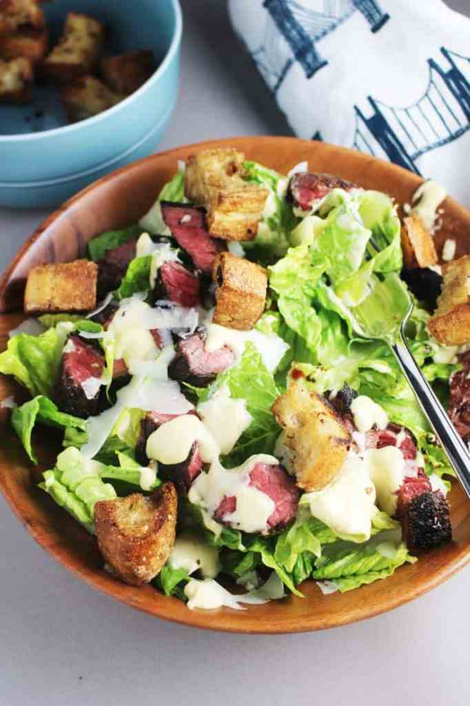 Caesar salad recipe with steak in a wooden bowl