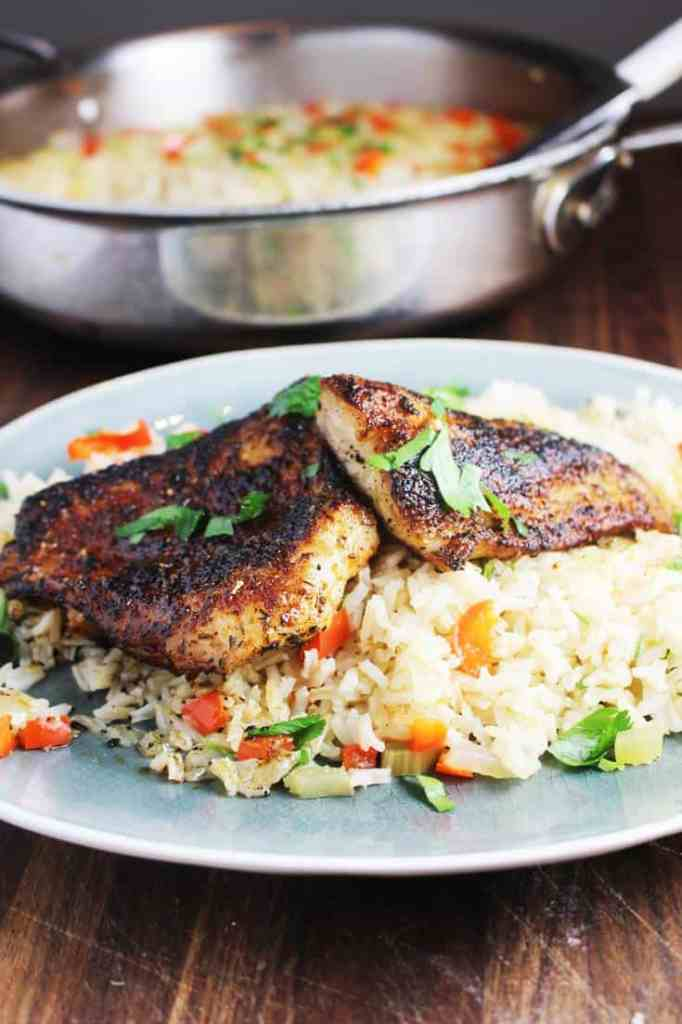 Cajun blackened fish recipe over rice pilaf on a plate
