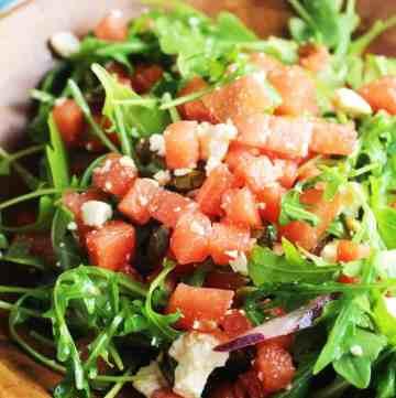 Watermelon arugula salad in a wooden bowl