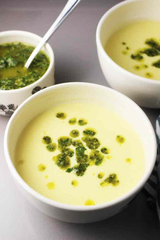 Fresh corn soup recipe in a bowl swirled with chimichurri