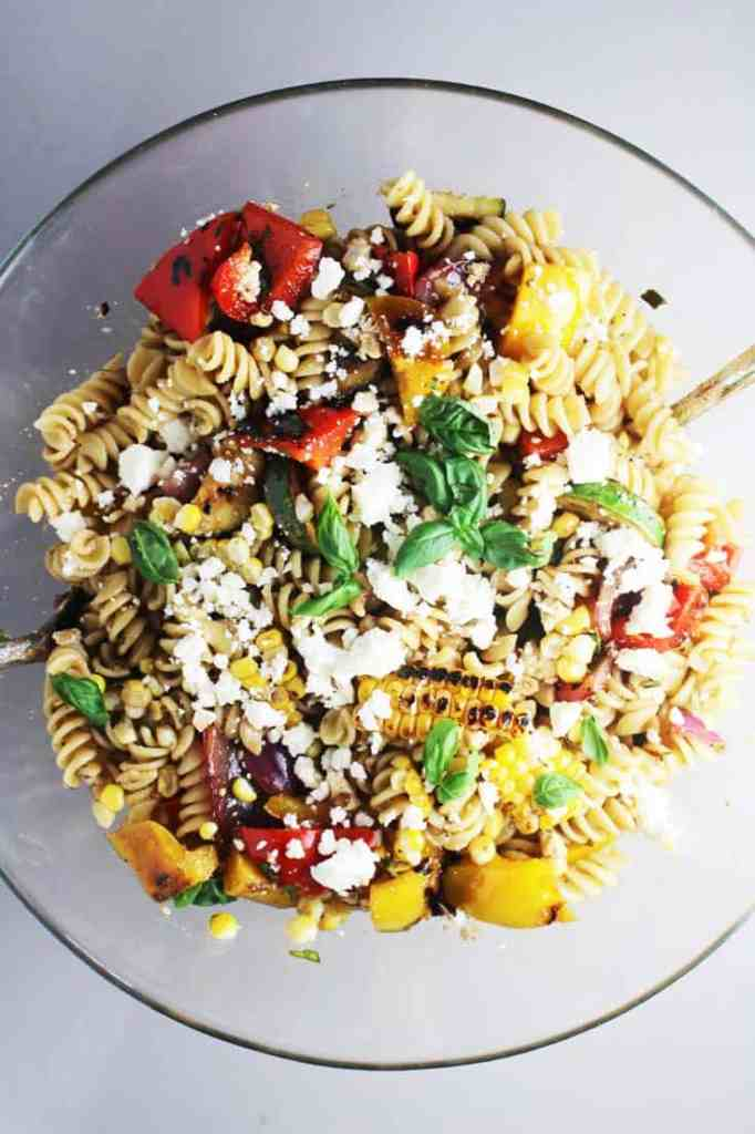 Summer pasta salad with grilled vegetables in a large glass serving bowl