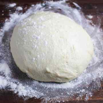 A ball of pizza dough on a floured wood counter